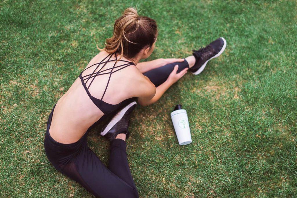 芝生でストレッチをする女性